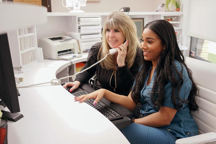 Kathy Salvatoriello and Kiana Burgos working the front desk at Harmony Dental Arts