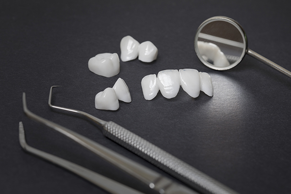 four different sets of dental lumineers placed in the center of dental tools